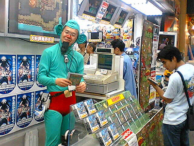 Man dressed up as Tingle behind the sales counter of Japanese game store